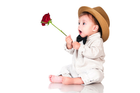 Emotional surprised toddler boy in retro, bow-tie hat and with red rose on white background.