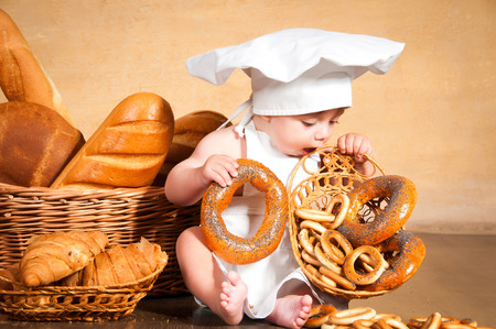 Little cook in a chef's hat eats bagels near wicker baskets of pastries and bakery products