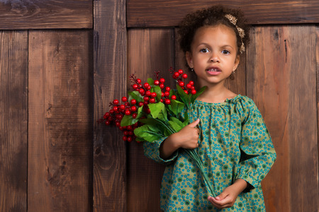 considerate: Little african  girl in rural shirt with bunch of berries. Background of brown wooden wall Stock Photo