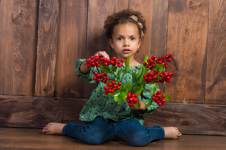barn girls: Little african  girl in rural shirt with bunch of berries. Background of brown wooden wall Stock Photo
