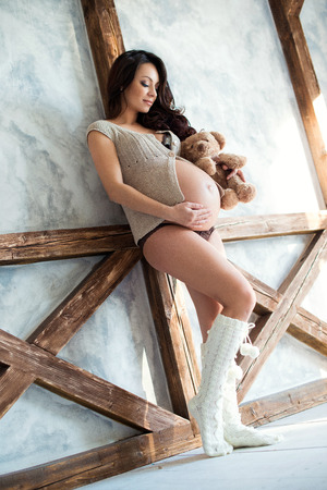 full height: Pregnant girl with teddy bear in the interior. Full height Stock Photo