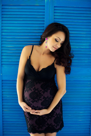 Pregnant brunette girl with long hair embraces the stomach on a background of blue wooden wall Stock Photo