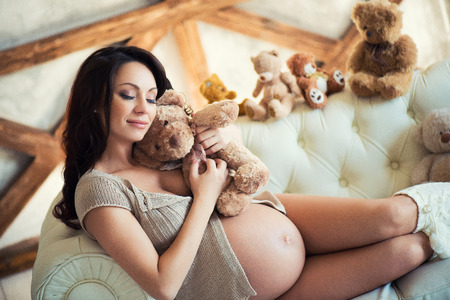 Pregnant girl with brown teddy bear sitting on the couch. Love and Motherhood Stock Photo