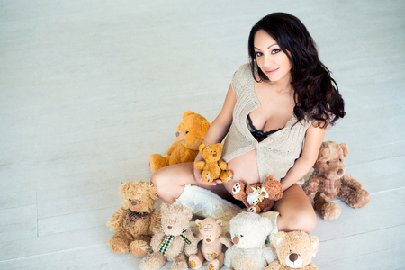 warm house: Pregnant girl sitting on the warm floor with teddy bears. The concept of warm house, housing problem, repair Stock Photo