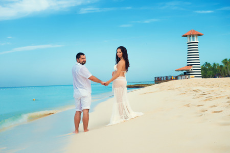 dominican: Beautiful young pregnant couple on the Caribbean coast. Happy pregnancy
