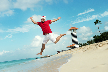 'grandfather frost': Santa Claus and wish a happy new year. Funny Grandfather Frost jumps on the sea. Tropical sandy beach - xmas travel vacation discounts and travel agencies price reductions concept