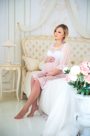 bed clothes: Beautiful pregnant girl in a home clothes sitting in the interior on a bed of roses