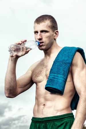 respite: Muscular young man after a workout  drinking  bottle of water