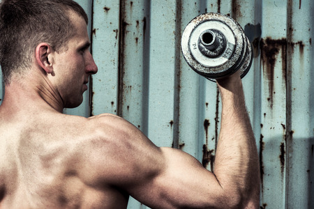 powerfully: Close up young athletic man doing workout with heavy dumbbell against the background of agray metal wall