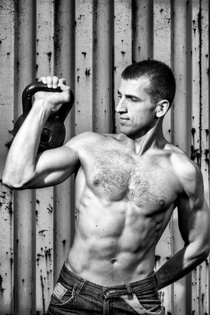 powerfully: Young athlete man doing workout with heavy weights on the background of a gray metal wall