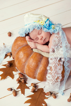cinderella pumpkin: Tale of Cinderella. Little beautiful newborn baby girl in a bonnet sleeping on a pumpkin