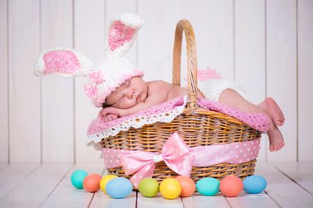 pascuas navide�as: El beb� reci�n nacido en un traje de conejo tiene sue�os dulces en la cesta de mimbre. Pascua vacaciones Foto de archivo