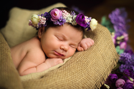Beautiful newborn baby girl with a purple wreath sleeps in a wicker basket Фото со стока
