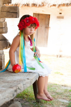 ukrainian ethnicity: Ukrainian girl in a wreath of red flowers on a bench with an apple in his hand