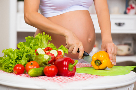 Close-up of a pregnant belly. Pregnant woman in the kitchen preparing a vegetable salad.