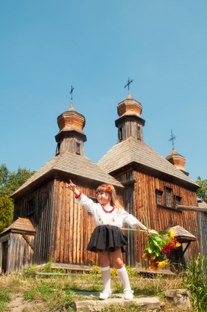 Wooden old church. Little Ukrainian girl. National Museum of Folk Architecture and Life Pirogovo