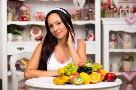 Beautiful brunette girl sitting at the kitchen table with a plate of fresh fruit. Diet, healthy food and vitamins