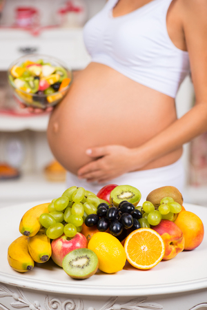 Close-up of a pregnant  tummy with fresh fruit and plate of salad. Healthy pregnancy, diet and vitamins