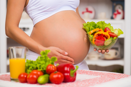 Close-up of a pregnant belly. Women's Health, fortified food. Fresh vegetables, diet and figure Stockfoto