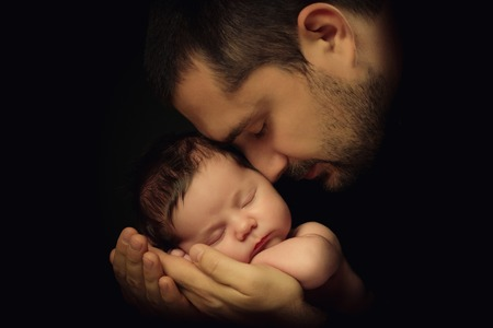 Little 15 days old baby lying securely on his Dads arms, against a black background. Stock Photo