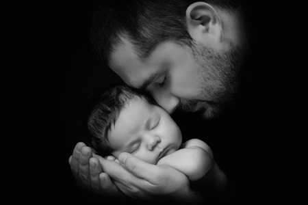 cradling: Little 15 days old baby lying securely on his Dads arms, against a black background. Stock Photo