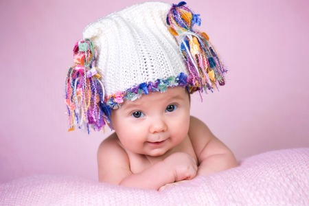 Beautiful little baby girl wearing pink knitted cap. Stock Photo