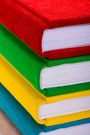 side table: Multicolored book textile cover. Photobooks on a white background