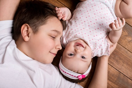vernacular: Brother hugging his newborn sister. View from above.