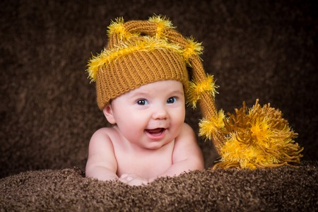Newborn in a knitted winter hat on a beige background.