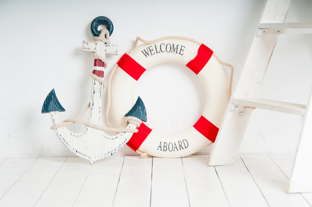 Anchor and life buoy on a white wooden floor