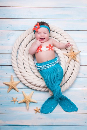 The newborn girl is crying in a mermaid suit the ropes on wooden boards. Stock Photo
