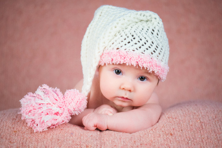 Newborn baby in a warm knitted hat.