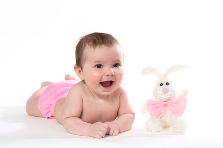 Little girl smiling with a toy rabbit lies on white background.