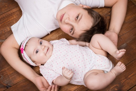 vernacular: Brother hugging his newborn sister. View from above