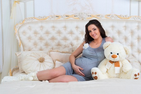 Beautiful pregnant brunette sitting on a bed with teddy bear.