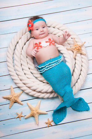 The newborn girl in a mermaid costume, lies in the ropes on wooden boards. Stock Photo