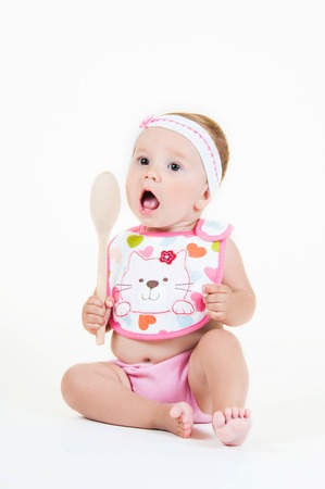 Little girl surprised with a spoon isolated on white background.