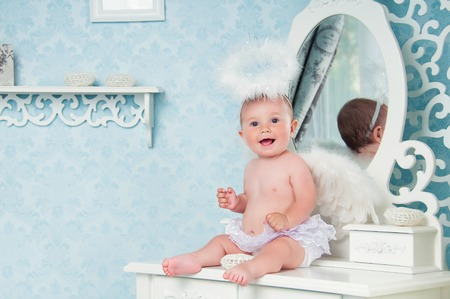 Little angel smiling and sitting on the dressing table
