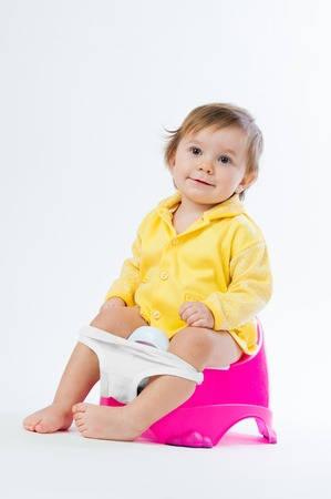 Little smiling girl sitting on a pot. Isolated on white background. Stock Photo
