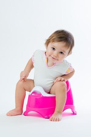 La niña sonriente sentado en una olla. Aislado en el fondo blanco. Foto de archivo - 73948490
