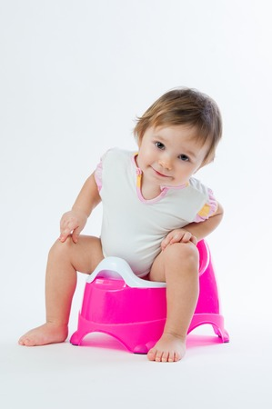 Little smiling girl sitting on a pot. Isolated on white background. Archivio Fotografico