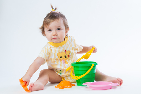 Cute baby with bucket and spade isolated on white background