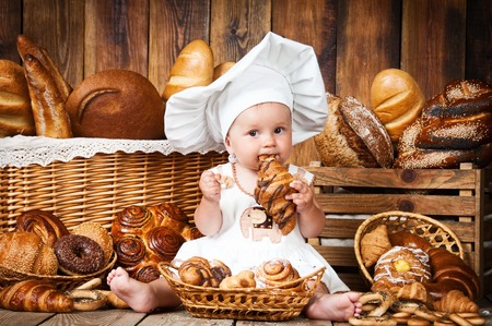 Small child cooks a croissant in the background of baskets with rolls and bread.