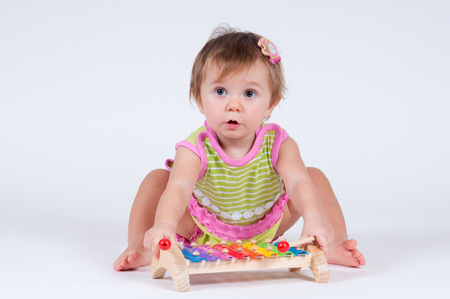 Girl with excitement playing on a xylophone isolated on white