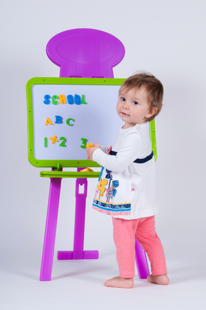 play date: A little girl is standing near the board with letters and numbers. Stock Photo