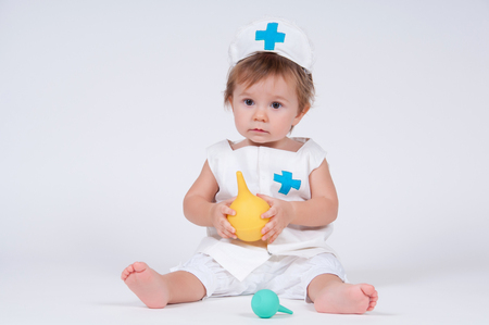 Girl laughs playing nurse with enema in hands Stock Photo