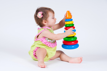 gifted: Cute little girl playing with a toy pyramid