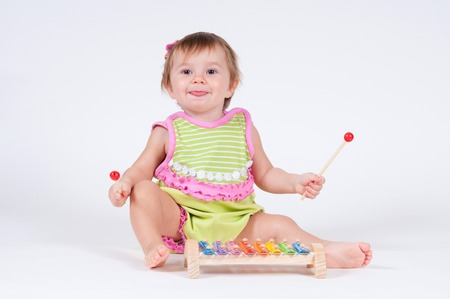 xilofono: Girl with excitement playing on a xylophone isolated on white