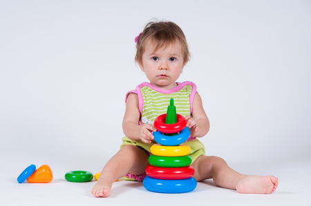 Cute little girl playing with a toy pyramid