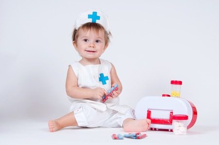 The girl laughs while playing a nurse with pills